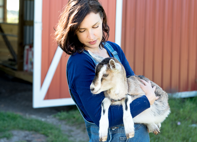 "woman wearing overalls holding a goat"" style="