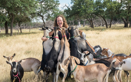smiling woman surrounded by goats
